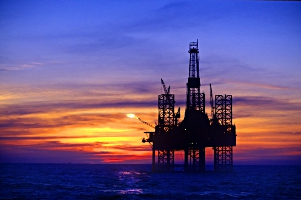Silhouette of oil platform in sea against moody sky at sunset